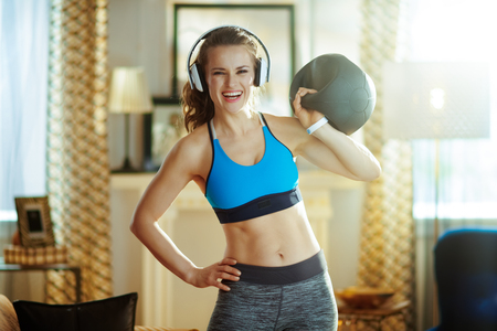 happy active woman in headphones in sport clothes with functional training gear in the modern house. Stock Photo