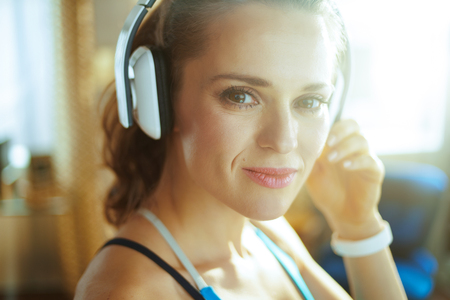 pensive active sports woman in fitness clothes listening to the music with headphones in the modern house.