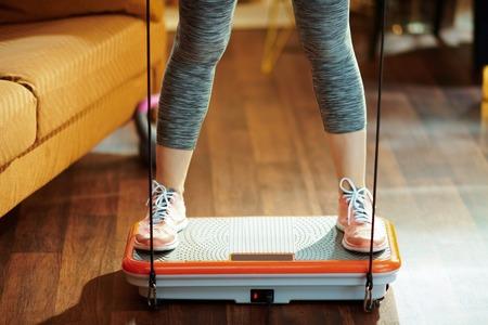 Nahaufnahme auf passender Sportfrau in Fitnesskleidung beim modernen Heimtraining mit Vibrationsplatte