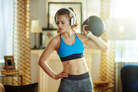 fit sports woman in headphones in sport clothes in the modern house doing functional training exercises. Stock Photo