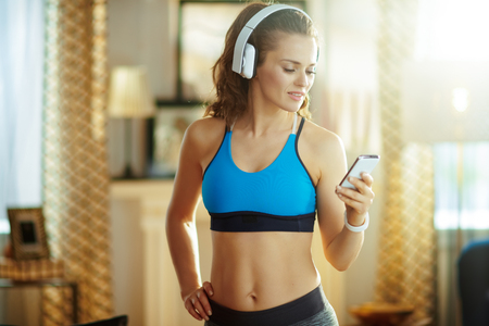 young sports woman in headphones in fitness clothes in the modern house using smartphone to track heart rate in fitness app.