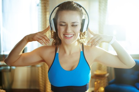 Portrait of smiling healthy woman in fitness clothes listening to the music with headphones at modern home.
