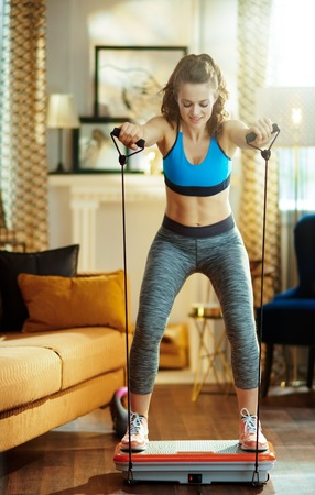 smiling healthy woman in fitness clothes at modern home training using vibration power plate. Stock Photo