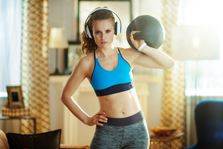 healthy woman in headphones in fitness clothes with functional training gear at modern home.