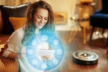 happy fit housewife with long brunette hair in the modern house using smart home application on tablet PC and robot vacuum cleaning floor in background. Stock Photo