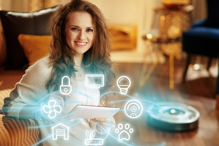 Portrait of smiling young woman with long brunette hair in the modern house using smart home application on tablet PC and robot vacuum cleaning floor in background.