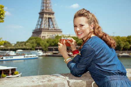 happy stylish solo traveller woman in blue jeans overall taking photos with retro photo camera in Paris, France.