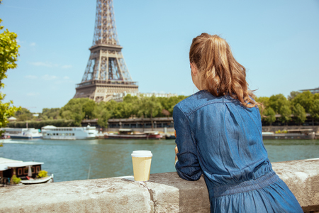Seen from behind young tourist woman in blue jeans overall with cup of coffee sightseeing not far from Eiffel tower in Paris, France.