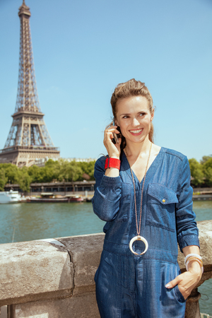 smiling young woman in blue jeans overall near the parapet on the embankment of the river Seine overlooking Eiffel tower in Paris, France talking on a smartphone. Banco de Imagens
