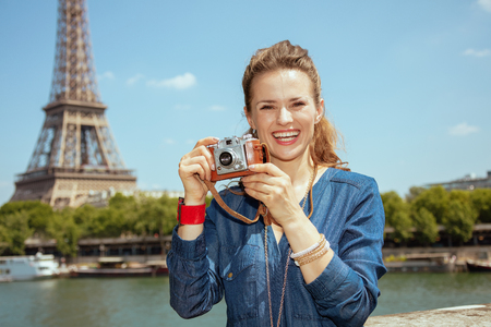 happy modern solo traveller woman in blue jeans overall taking photos with retro photo camera not far from Eiffel tower in Paris, France. Banco de Imagens