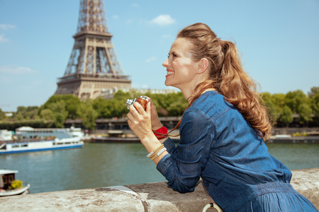 smiling elegant tourist woman in blue jeans overall with retro photo camera looking into the distance near the parapet on the embankment of the river Seine overlooking Eiffel tower in Paris, France.