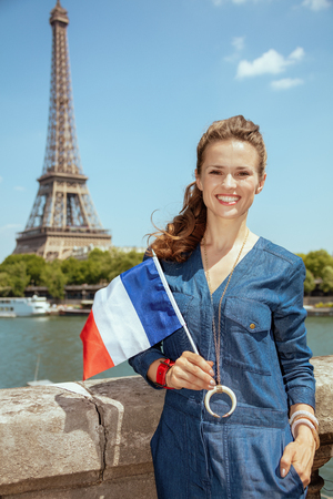 Portrait of smiling elegant tourist woman in blue jeans overall with France flag against clear view of the Eiffel Tower and river Seine in Paris, France.