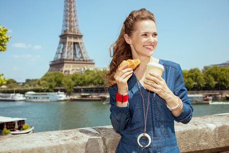 happy modern solo traveller woman in blue jeans overall with cup of coffee and croissant looking aside not far from Eiffel tower in Paris, France.