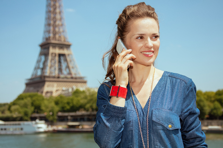 happy stylish woman in blue jeans overall near the parapet on the embankment of the river Seine not far from Eiffel tower in Paris, France speaking on a mobile phone.
