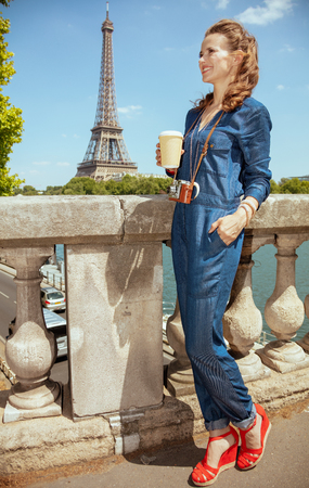 Full length portrait of happy trendy woman in blue jeans overall with retro film photo camera and coffee cup sightseeing in Paris, France.