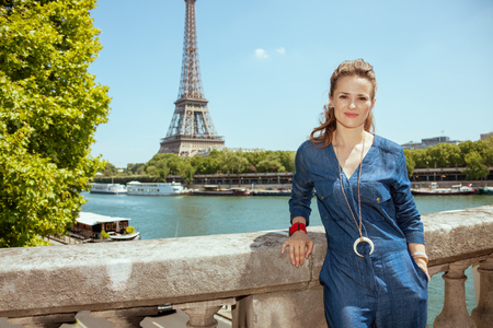Portrait of happy elegant tourist woman in blue jeans overall in Paris, France. Imagens