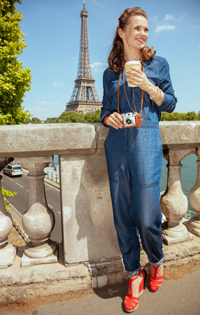 Full length portrait of smiling modern solo traveller woman in blue jeans overall with retro film photo camera and coffee cup near the parapet on the embankment of the river Seine not far from Eiffel