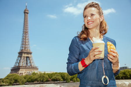 happy elegant solo traveller woman in blue jeans overall with coffee cup and croissant having excursion in Paris, France. Imagens