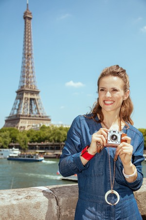 happy elegant traveller woman in blue jeans overall with retro photo camera looking into the distance near the parapet on the embankment of the river Seine not far from Eiffel tower in Paris, France. Banco de Imagens