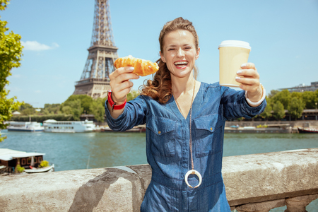 happy young woman in blue jeans overall near the parapet on the embankment of the river Seine overlooking Eiffel tower in Paris, France showing cup of coffee and croissant.