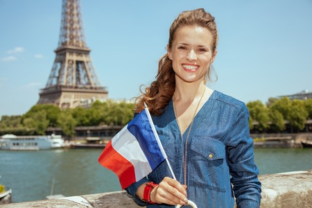 Portrait of happy trendy traveller woman in blue jeans overall with France flag not far from Eiffel tower in Paris, France. Stock Photo
