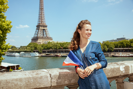 smiling stylish tourist woman in blue jeans overall with France flag exploring attractions near the parapet on the embankment of the river Seine not far from Eiffel tower in Paris, France.