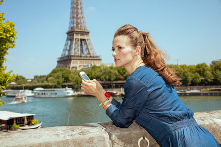 concerned modern solo tourist woman in blue jeans overall with smartphone using applications not far from Eiffel tower in Paris, France.