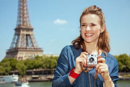 happy stylish solo tourist woman in blue jeans overall with retro photo camera looking into the distance not far from Eiffel tower in Paris, France. Imagens