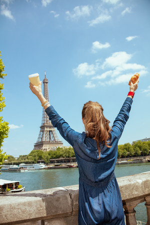 smiling modern solo tourist woman in blue jeans overall with cup of coffee and croissant rejoicing not far from Eiffel tower in Paris, France. Фото со стока