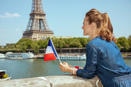Seen from behind stylish traveller woman in blue jeans overall with France flag sightseeing near the parapet on the embankment of the river Seine not far from Eiffel tower in Paris, France. Stock Photo