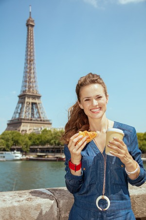 happy trendy solo traveller woman in blue jeans overall with cup of coffee and croissant in Paris, France.