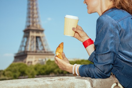 Closeup on smiling modern solo traveller woman in blue jeans overall not far from Eiffel tower in Paris, France having coffee cup and croissant. Stock Photo