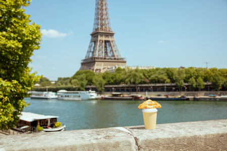 cup of coffee and croissant on the parapet at the embankment of the river Seine not far from Eiffel tower in Paris, France.
