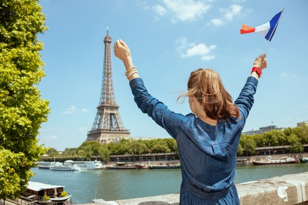 Seen from behind young tourist woman in blue jeans overall with France flag rejoicing in Paris, France.