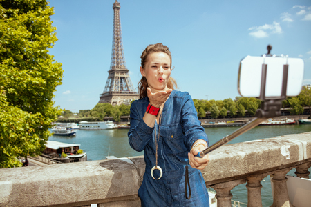 modern woman in blue jeans overall near the parapet on the embankment of the river Seine not far from Eiffel tower in Paris, France taking selfie using selfie stick and blowing air kiss. Stock Photo