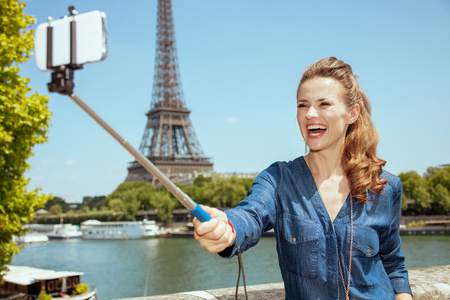 smiling young solo tourist woman in blue jeans overall not far from Eiffel tower in Paris, France taking selfie using selfie stick.