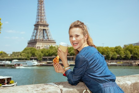 smiling stylish traveller woman in blue jeans overall with cup of coffee and croissant near the parapet on the embankment of the river Seine overlooking Eiffel tower in Paris, France.