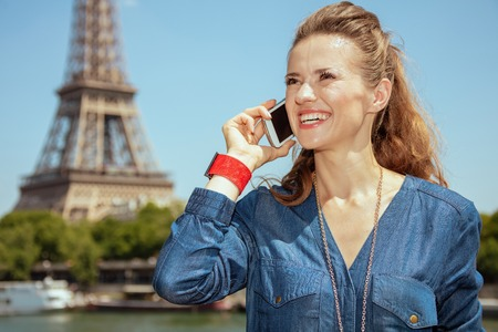 smiling modern solo tourist woman in blue jeans overall near the parapet on the embankment of the river Seine not far from Eiffel tower in Paris, France looking into the distance and using a smartphone. Imagens