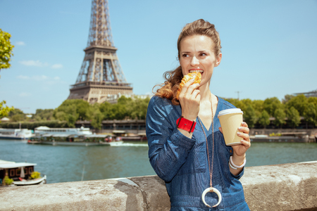 smiling young woman in blue jeans overall with cup of coffee eating croissant against clear view of the Eiffel Tower and river Seine in Paris, France.