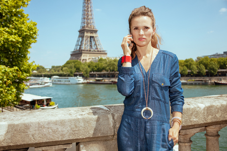 concerned trendy solo tourist woman in blue jeans overall near the parapet on the embankment of the river Seine not far from Eiffel tower in Paris, France talking on a smartphone. Imagens