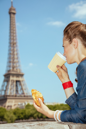 trendy solo traveller woman in blue jeans overall not far from Eiffel tower in Paris, France having coffee cup and croissant.