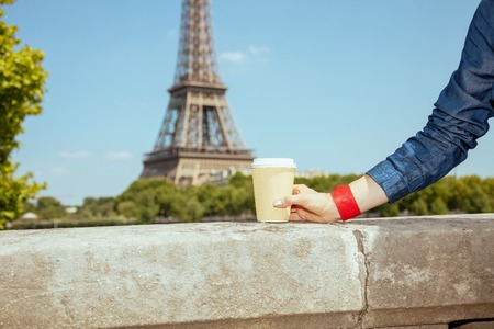 Closeup on smiling coffee cup in hand of tourist woman not far from Eiffel tower in Paris, France.