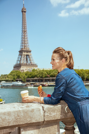 smiling young tourist woman in blue jeans overall with cup of coffee and croissant exploring attractions not far from Eiffel tower in Paris, France. Фото со стока