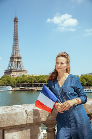 pensive trendy woman in blue jeans overall with France flag looking into the distance in Paris, France.