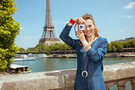 smiling young tourist woman in blue jeans overall taking photos with retro photo camera near the parapet on the embankment of the river Seine not far from Eiffel tower in Paris, France.