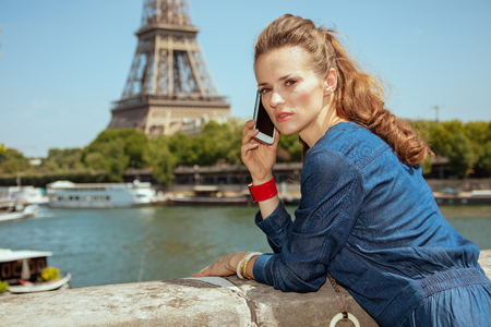 concerned stylish traveller woman in blue jeans overall in Paris, France talking on a smartphone.