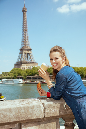 happy elegant woman in blue jeans overall with cup of coffee and croissant exploring attractions against clear view of the Eiffel Tower and river Seine in Paris, France.