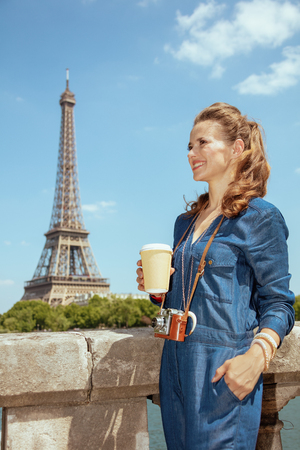happy modern solo traveller woman in blue jeans overall with retro film photo camera and coffee cup sightseeing in Paris, France. Imagens