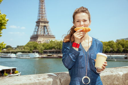 happy stylish woman in blue jeans overall with cup of coffee making smile with croissant in Paris, France.