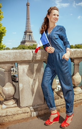 Full length portrait of happy modern solo tourist woman in blue jeans overall with France flag sightseeing not far from Eiffel tower in Paris, France. 写真素材